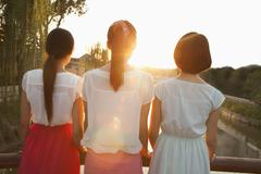 Three Young Women Looking Downstream at a Sunset - stock photo