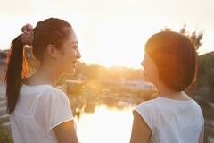 Two Young Women Looking at Sunset Stock Photos