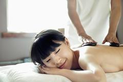 Young Woman Receiving Hot Stone Massage - stock photo