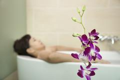 Woman Bathing with Orchid in Foreground Stock Photos