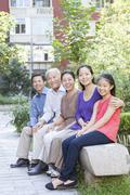 Three Generation Family Sitting in their Apartment Courtyard Stock Photos