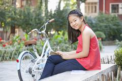 Young Girl Writing in a Courtyard with Her Bike - stock photo