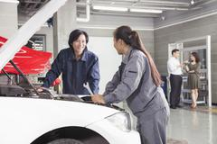 Mechanics and Customers in Auto Repair Shop Stock Photos