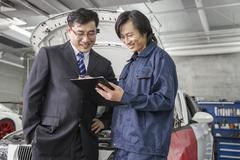 Businessman with Mechanic in Auto Repair Shop - stock photo