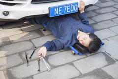 Male Mechanic working under the Car - stock photo