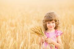 happy child holding wheat ears - stock photo