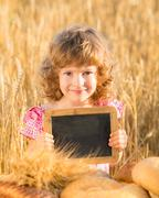 happy child with bread in field - stock photo