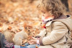 child feeds a little squirrel - stock photo