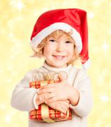 baby holding christmas gift in hands - stock photo
