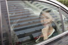 Stock Photo of Smiling Businesswoman in Car Back
