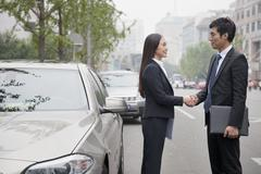 Business People Shaking Hands On Road - stock photo