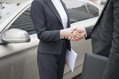 Stock Photo of Business People Shaking Hands By Car