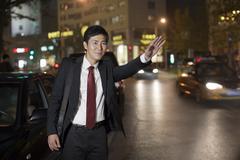 Businessman Hailing Taxi Cab - stock photo
