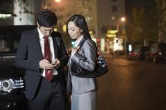Two Business People Looking At Cell Phone - stock photo