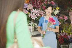 Florist Giving Bunch Of Flowers To Customer Stock Photos