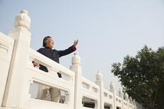 Senior man practicing Taijiquan in Beijing, arms in front - stock photo