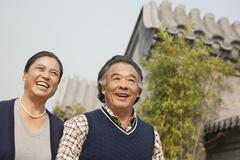 Happy senior couple walking outdoors by traditional building in Beijing - stock photo