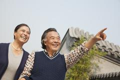 Happy senior couple outdoors pointing by traditional building in Beijing - stock photo
