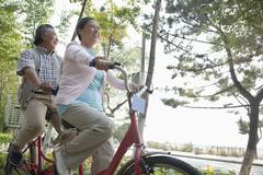 Stock Photo of Older couple riding tandem bicycle, Beijing