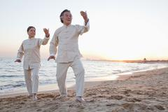 Two older people practicing Taijiquan on the beach at sunset, China - stock photo