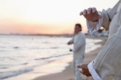 Two older people practicing Taijiquan on the beach at sunset, close up on hands Stock Photos