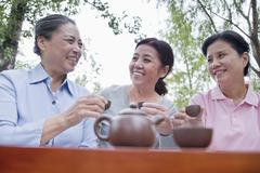 Group of mature women drinking Chinese tea in the park Stock Photos