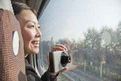 Young Woman Taking Photographs Outside Train Window - stock photo
