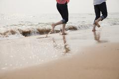 Stock Photo of Young Couple Running in the Waves