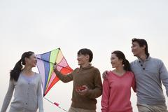 Young Friends Flying a Kite on the Beach - stock photo