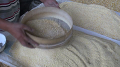 Sorting fine maize with wooden sieve at Uzbek bazaar Stock Footage