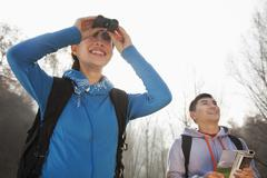 Young woman looking through binoculars, man standing in the background - stock photo