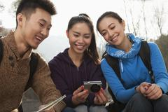 Friends looking at the picture on the screen of digital camera - stock photo