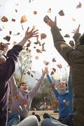 Stock Photo of Group of young people throwing leaves