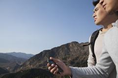 Men hiking and using GPS - stock photo