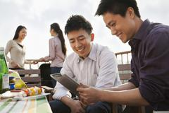 Friends Using Digital Tablet at Rooftop Barbecue - stock photo
