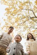 Family holding hands and walking through the park in the autumn, low angle view - stock photo