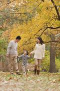 Family walking through the park in the autumn Stock Photos