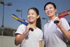 Mother and daughter playing tennis - stock photo