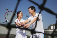 Young girl playing tennis with her coach Stock Photos