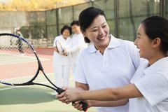 Young girl playing tennis with her coach - stock photo