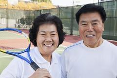 Mature couple playing tennis, portrait Stock Photos