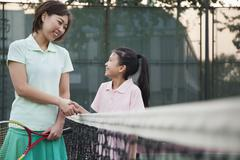 Mother and daughter handshaking over the tennis net Stock Photos