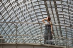 Charming young woman in a fashionable cloak is posing under the tracery roof Stock Photos