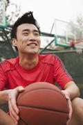 Young man sitting with a basketball on the basketball court, portrait Stock Photos