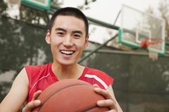 Young man sitting with a basketball on the basketball court, portrait - stock photo