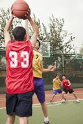 Two teams playing basketball - stock photo