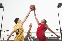 Basketball players fighting for a ball Stock Photos