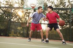 Two street basketball players on the basketball court Stock Photos