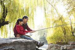 Stock Photo of Grandfather and grandson fishing portrait at lake