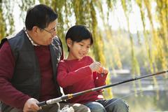 Grandfather and grandson putting lure on fishing line Stock Photos